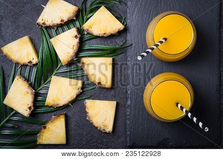 Sliced Pineapple And Pineapple Juice Or Smoothies On A Black Background.