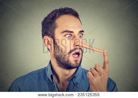 Man With Long Nose Isolated On Grey Wall Background. Liar Concept. Human Face Expressions, Emotions,