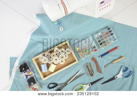 Sewing Machine And Colorful Thread Rolls, Scissors, Fabric And Accessories For Sewing On White Backg
