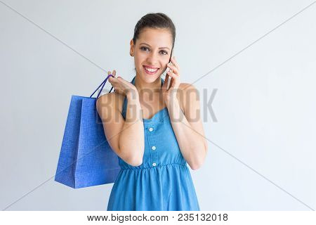 Happy Attractive Shopaholic Talking On Phone And Looking At Camera. Cheerful Excited Young Woman Hol