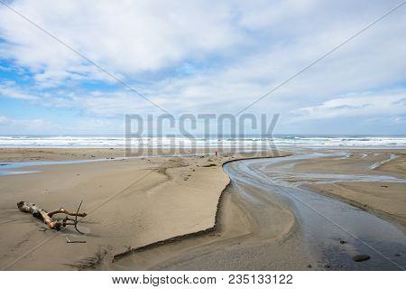Sandy Ocean Beach With Driftwood, Seaweed, Creek, Blue Cloudy Sky, Waves, Dog And Walker On Oregon C