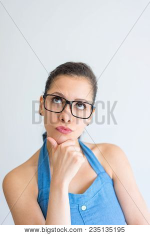 Pensive Intelligent Young Woman Touching Chin And Looking Up. Thoughtful Pretty Girl Deep In Thought