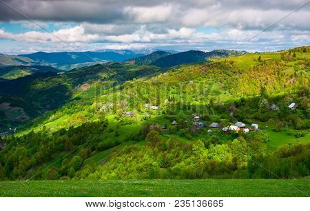 Village On A Forested Hillside In Springtime. Beautiful Rural Scenery Of Carpathian Mountains On A C