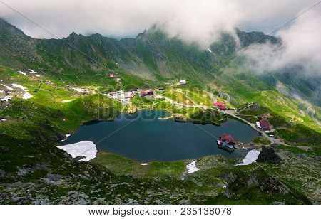 Area Of Lake Balea In Clouds. Gorgeous Summer Landscape Of Fagarasan Mountains, Romania. Popular Tou