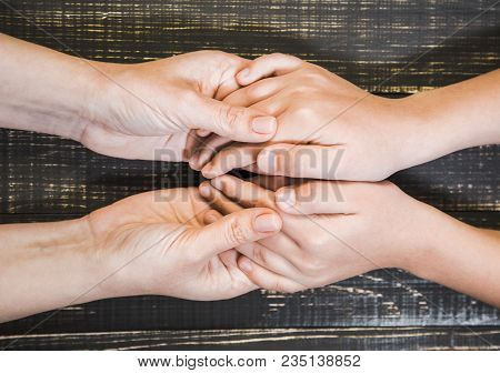 Closeup Top View Of Human Hands Of Adult Woman And Little Child Isolated On Brown Wooden Background.