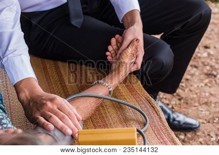 Male Doctor Listening Heart Beat And Breathing Of Elderly Woman With Stethoscope With First Aid Medi