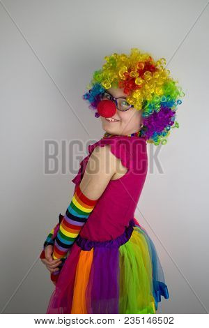 Little Girl With Glasses And Red Nose In Colorful Clown Costume.little Girl In Clown Costume.