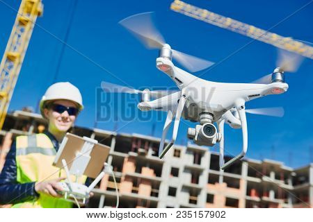Drone operated by construction female worker on building site