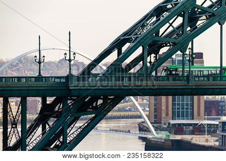 Green Bus Crossing The Tyne Bridge And Millenium Bridge In The Distance At Newcastle Quayside On A C