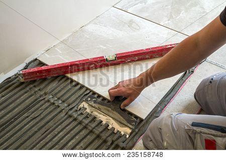 Ceramic Tiles And Tools For Tiler. Worker Hand Installing Floor Tiles. Home Improvement, Renovation