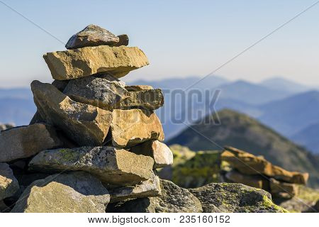 Stack Of Stones Covered With Moss On Top Of A Mountain On Mountains Background. Concept Of Balance A