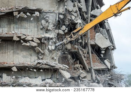Dismantling Of A House. Building Demolition And Crashing By Machinery For New Construction. Industry