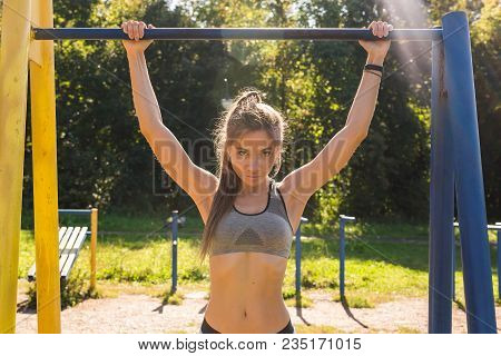 Fit Woman Doing Pull-ups. Young Athletic Fitness Woman Working Out At Outdoor Gym Doing Pull Ups At