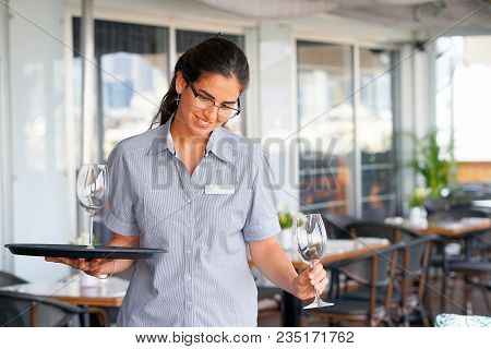 A Barmaid Girl Carries A Wine Glasses On A Tray To The Client Of The Hotel Bar. The Waitress Carries