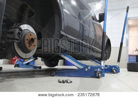 Hydraulic floor jacks under a black car without a wheel in the car workshop