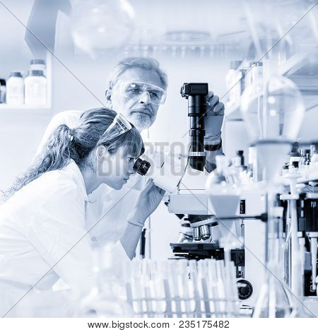 Health Care Researchers Microscoping In Life Science Laboratory. Young Female Research Scientist And