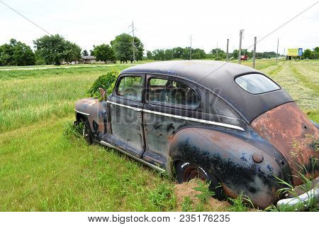 Abandoned Rusty Old Car Sitting In A Field And Overgrown With Greenery.
