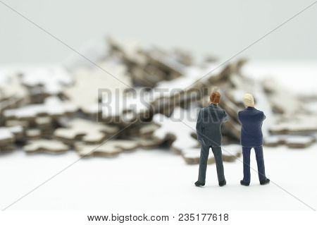 Miniature People  Businessmen Standing Investment Analysis  Or Investment In Solve Puzzles To Find A