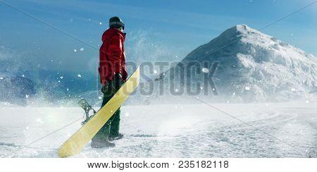 Snowboarder holds board in hands, winter sport
