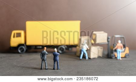 Miniature Business Man Looking At  Workers Carrying Products Goods Box To Container Truck In Distrib