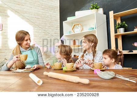 Adorable Family Gathered Together At Home, Drinking Tea With Appetizing Cupcakes And Chatting Animat