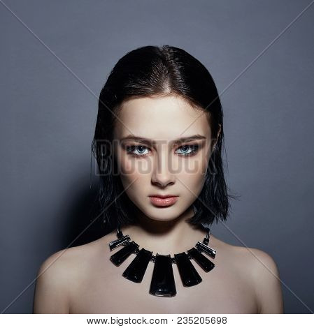 Sexy Brunette Girl Has Black Hair Jewels Around Her Neck And In Her Ears, Big Blue Eyes. Summer Skin