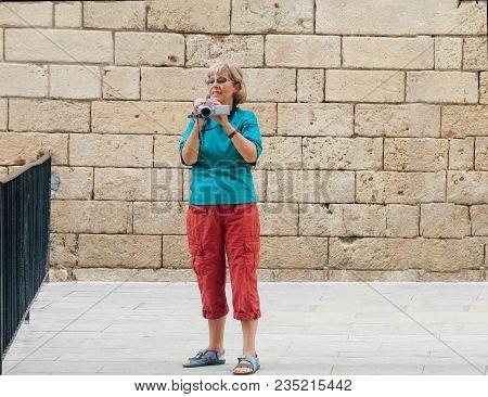 Beautiful Mature Tourist Woman Travelling In Palma De Majorca Screens Movie On Old Video Camera
