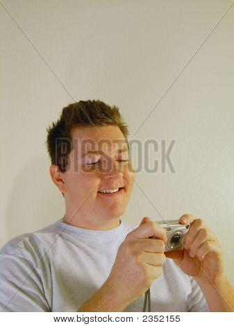 Smiling Man With A Digital Compact Camera