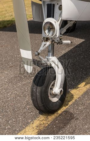 A Bow Of A Small Sport Aircraft. Wheel Of Airplane. Close Up Of Aircraft Wheel On Runway. Plane Whee