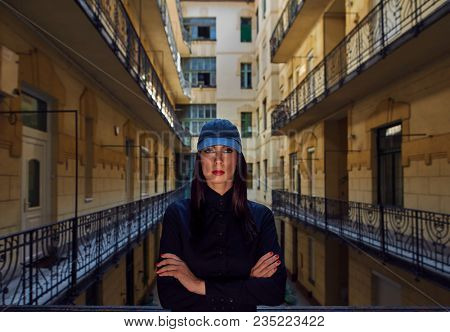 Woman in black standing in courtyard wearing black baseball cap, Unusual portrait photo.