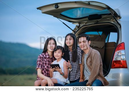 Happy Little Girl  With Asian Family Sitting In The Car For Enjoying Road Trip And Summer Vacation I