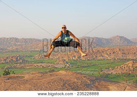 Handsome High Jump Man. A Bald Man Wearing Sunglasses In Hampi, Jumps High On Anjaneya Hill, Hanuman