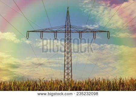 High Voltage Mast Om A Crn Field And Rainbow In The Sky. Concept Renewable Resources