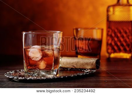 Glass Of Scotch Whiskey With Natural Ice And Cigar On Old Wooden Table.
