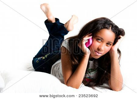 Concerned teenage girl on a pink cell phone lying down listening with legs crossed feet in the air - isolated on white poster