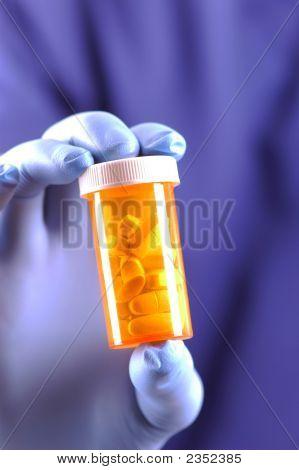 Gloved Hand Holding Pill Bottle