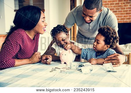 Family saving money to piggy bank
