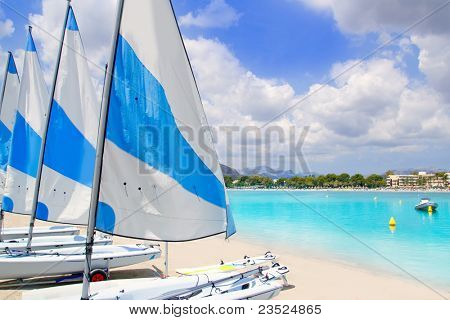 Beach of Puerto de Alcudia in Mallorca with little sailboats and white sand in Majorca