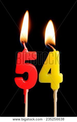 Burning Candles In The Form Of 54 Fifty Four (numbers, Dates) For Cake Isolated On Black Background.