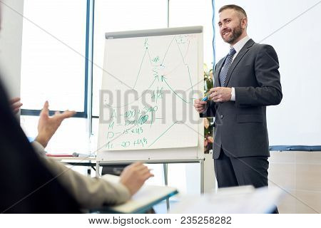 Portrait Of Smiling Bearded Business Coach Standing By Whiteboard Giving Presentation For Audience