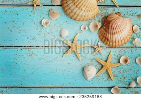 seashells and sand on blue wooden background