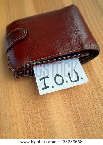 A Battered Wallet With A Note Sticking Out Of It On Which Someone Has Written Iou As A Concept For M