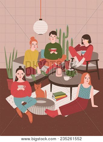 Group Of Young Women Sitting In Room Furnished In Scandinavian Style, Drinking Tea And Talking To Ea