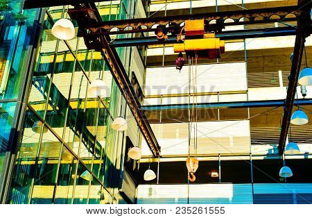 A modern glass window building under construction with a crane and metal beams.