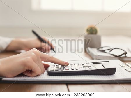 Closeup Of Woman Hand Counting On Calculator And Writing In Documents. Financial Background, Count A