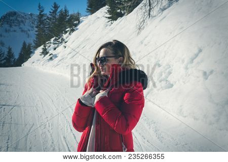 Attractive Young Woman In A Colorful Red Jacket And Sunglasses Standing On A Snowy Mountain Road In
