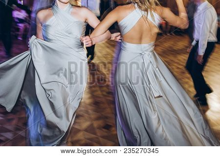 Happy Stylish Bride And Bridesmaids Dancing And Having Fun At Wedding Reception In Restaurant. Guest