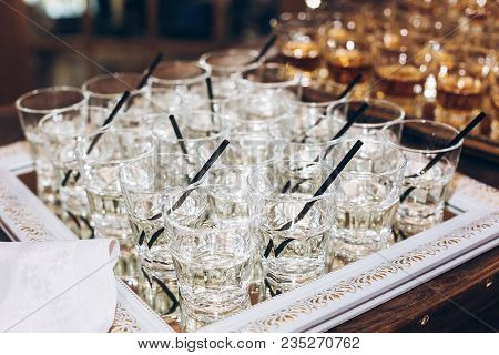 Stylish Glasses With Martini Or Jin With Black Straw On Table At Wedding Reception. Alcohol Bar. Tas