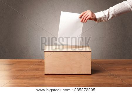 Ballot box with person casting vote on blank voting slip, grungy background