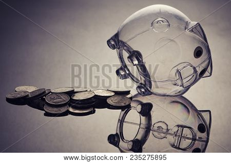 Problem With Saving Money Concept, Empty Piggybank And Coins On Reflection Table. Shot Under Low Lig